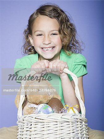 Portrait of a girl holding Easter eggs in a wicker basket Stock Photo - Premium Royalty-Free, Image code: 640-02766976