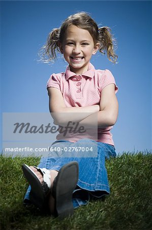 Portrait of a girl sitting with her arms crossed Stock Photo - Premium Royalty-Free, Image code: 640-02767004