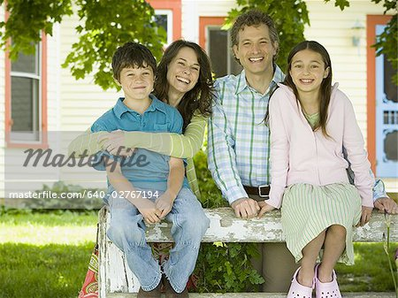 Portrait of a man and a woman smiling with their children Stock Photo - Premium Royalty-Free, Image code: 640-02767194