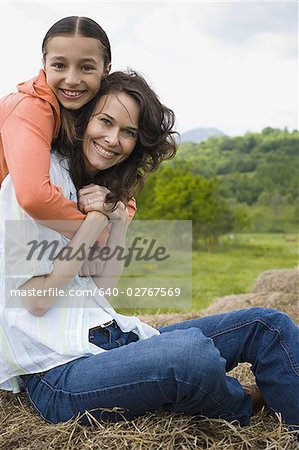 Portrait of a girl hugging her mother from behind Stock Photo - Premium Royalty-Free, Image code: 640-02767569