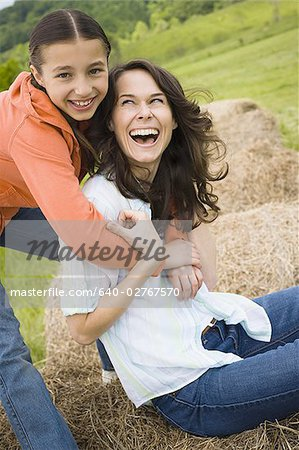 Portrait of a girl hugging her mother from behind Stock Photo - Premium Royalty-Free, Image code: 640-02767570