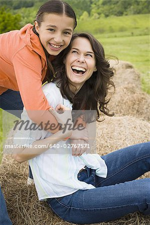 Portrait of a girl hugging her mother from behind Stock Photo - Premium Royalty-Free, Image code: 640-02767571