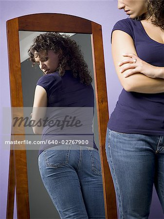 Young woman looking at her buttocks in the mirror Stock Photo - Premium Royalty-Free, Image code: 640-02767900