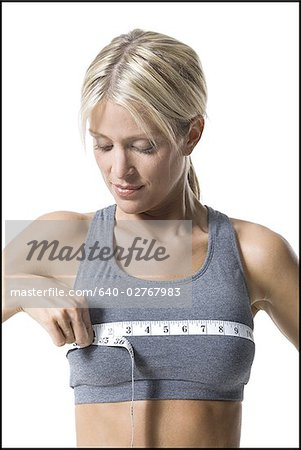 A young woman measuring her chest with a measuring tape Stock Photo - Premium Royalty-Free, Image code: 640-02767983