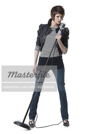 Portrait of a young woman holding a microphone and standing Stock Photo - Premium Royalty-Free, Image code: 640-02768426