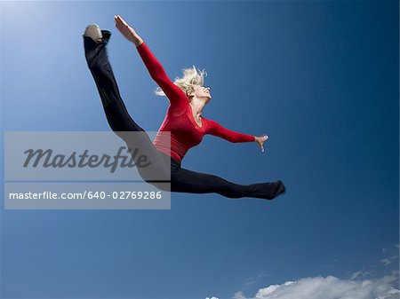 Woman jumping Stock Photo - Premium Royalty-Free, Image code: 640-02769286