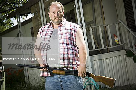 Overweight man with a shotgun Stock Photo - Premium Royalty-Free, Image code: 640-02769446