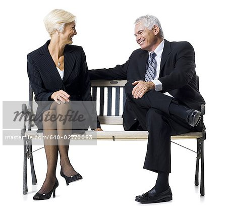 Businessman and businesswoman sitting on a bench Stock Photo - Premium Royalty-Free, Image code: 640-02770083