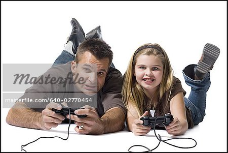 Father and daughter playing a video game Stock Photo - Premium Royalty-Free, Image code: 640-02770454