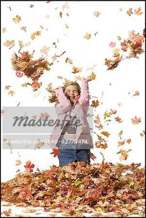 Young girl playing in fallen leaves Stock Photo - Premium Royalty-Free, Image code: 640-02770474