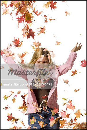Young girl playing in fallen leaves Stock Photo - Premium Royalty-Free, Image code: 640-02770475