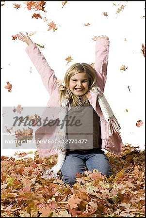 Young girl playing in fallen leaves Stock Photo - Premium Royalty-Free, Image code: 640-02770477