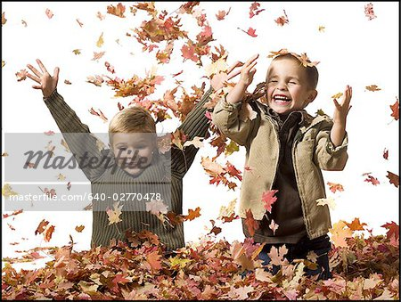 Young children playing in pile of fallen leaves Stock Photo - Premium Royalty-Free, Image code: 640-02770478