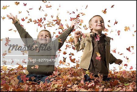Young children playing in pile of fallen leaves Stock Photo - Premium Royalty-Free, Image code: 640-02770479