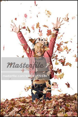 Young girl playing in fallen leaves Stock Photo - Premium Royalty-Free, Image code: 640-02770514