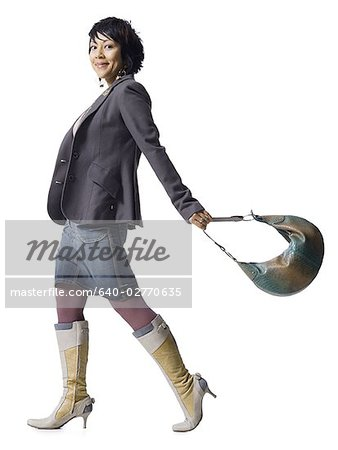 Woman with knee high boots and handbag Stock Photo - Premium Royalty-Free, Image code: 640-02770635