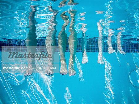 Feet dangling in swimming pool Stock Photo - Premium Royalty-Free, Image code: 640-02770644