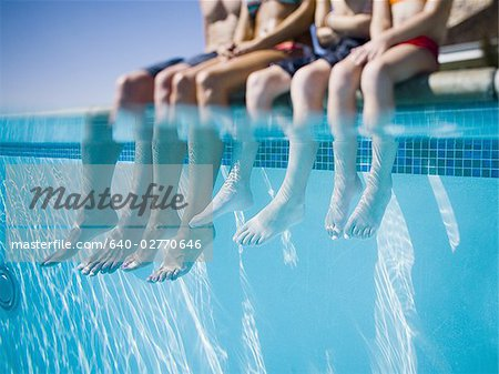 Feet dangling in swimming pool Stock Photo - Premium Royalty-Free, Image code: 640-02770646