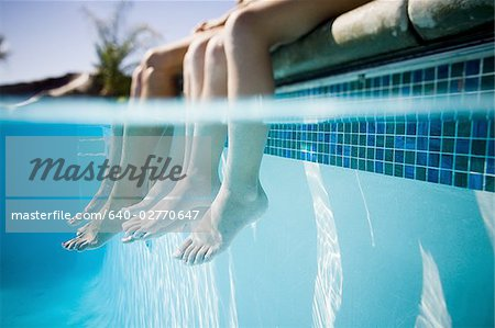 Feet dangling in swimming pool Stock Photo - Premium Royalty-Free, Image code: 640-02770647