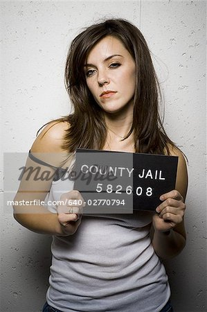 Mug shot of disheveled woman Stock Photo - Premium Royalty-Free, Image code: 640-02770794