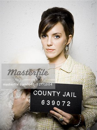 Mug shot of formally dressed woman with dog Stock Photo - Premium Royalty-Free, Image code: 640-02771004