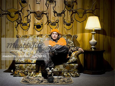 Man on sofa with antlers Stock Photo - Premium Royalty-Free, Image code: 640-02771060