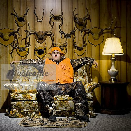 Man on sofa with antlers Stock Photo - Premium Royalty-Free, Image code: 640-02771061