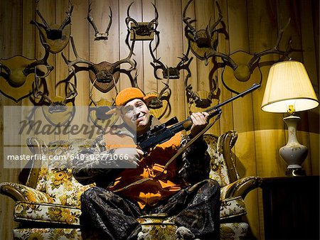 Man on sofa with rifle and antlers Stock Photo - Premium Royalty-Free, Image code: 640-02771066