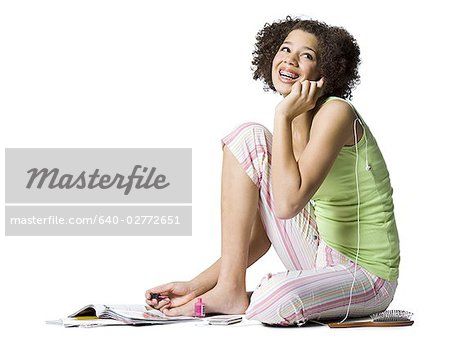 Teenage girl with braces talking on cell phone and painting toenails Stock Photo - Premium Royalty-Free, Image code: 640-02772651