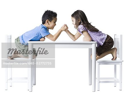 Boy and girl sitting at table arm wrestling Stock Photo - Premium Royalty-Free, Image code: 640-02772735