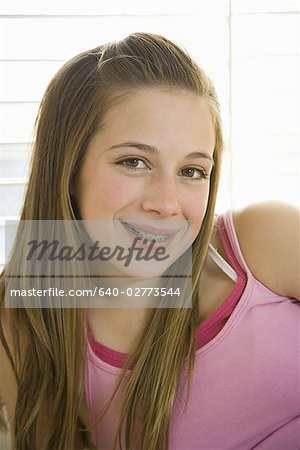 Girl with braces on bed with hairbrush smiling Stock Photo - Premium Royalty-Free, Image code: 640-02773544