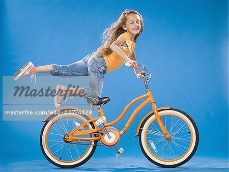 Girl on orange bicycle kneeling on seat with foot up Stock Photo - Premium Royalty-Free, Image code: 640-02774428