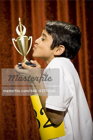 Boy kissing trophy cup Stock Photo - Premium Royalty-Free, Image code: 640-02774541
