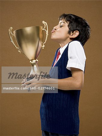 Boy kissing trophy cup Stock Photo - Premium Royalty-Free, Image code: 640-02774601