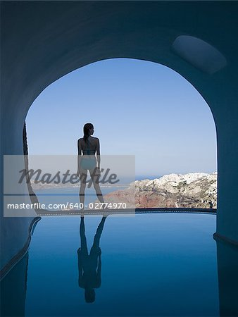 Silhouette rear view of woman in bikini standing at edge of infinity pool with arch and rock formation