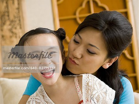 Mother giving daughter a kiss on cheek Stock Photo - Premium Royalty-Free, Image code: 640-02775112
