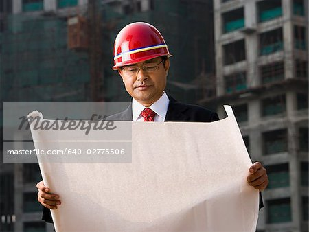 Construction site foreman with blueprints outdoors Stock Photo - Premium Royalty-Free, Image code: 640-02775506