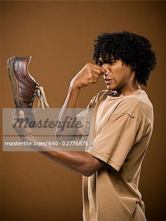 young man in a brown shirt holding a shoe and his nose. Stock Photo - Premium Royalty-Free, Image code: 640-02776875