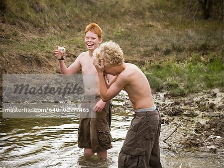 four boys playing in the woods. Stock Photo - Premium Royalty-Free, Image code: 640-02777465