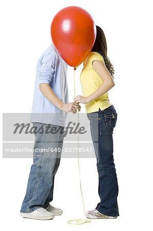 couple kissing behind a red balloon Stock Photo - Premium Royalty-Free, Image code: 640-02778547