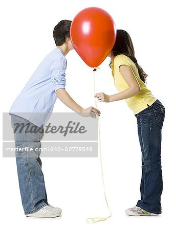 couple kissing behind a red balloon Stock Photo - Premium Royalty-Free, Image code: 640-02778548