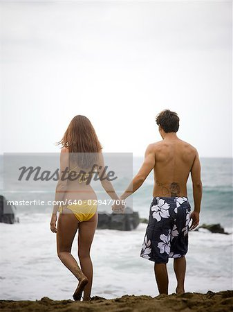 young couple at the beach holding hands Stock Photo - Premium Royalty-Free, Image code: 640-02947706