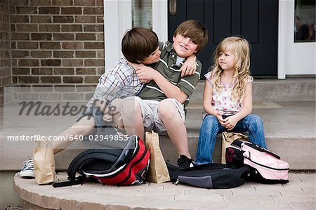 brothers fighting as little sister watches Stock Photo - Premium Royalty-Free, Image code: 640-02949853