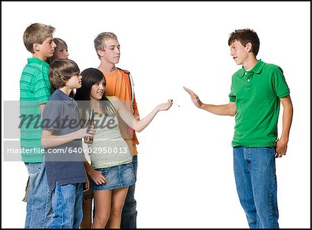 group of teenagers offering another a cigarette Stock Photo - Premium Royalty-Free, Image code: 640-02950013