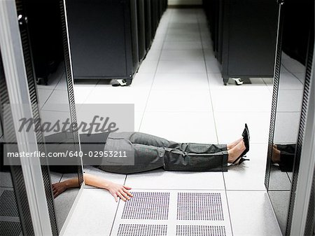 woman lying on the floor in a server room Stock Photo - Premium Royalty-Free, Image code: 640-02953211