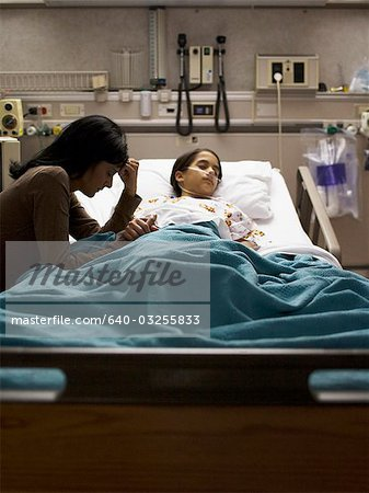 Mother sitting nervously by daughter in hospital bed Stock Photo - Premium Royalty-Free, Image code: 640-03255833