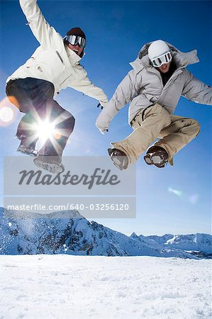 Two friends jumping outside in the snow Stock Photo - Premium Royalty-Free, Image code: 640-03256120