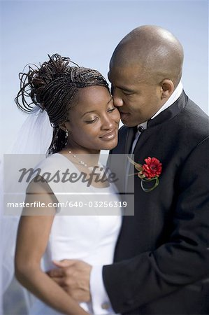 Close-up of a groom kissing his bride Stock Photo - Premium Royalty-Free, Image code: 640-03256319