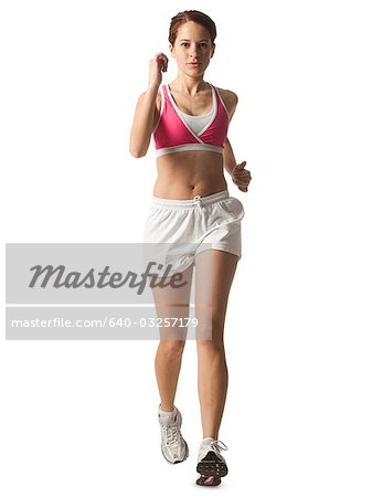 Young woman walking for exercise, studio shot Stock Photo - Premium Royalty-Free, Image code: 640-03257179