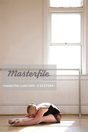 Springville, Utah, USA, Young ballet dancer stretching before training Stock Photo - Premium Royalty-Free, Image code: 640-03257484